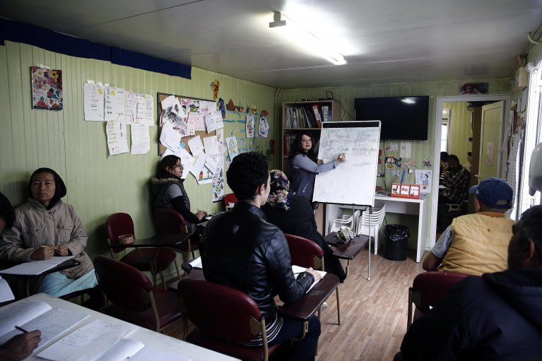 A volunteer giving Greek language lessons at the Eleonas refugee camp in Athens, Greece   Photo: EPA/Alexandros Vlachos