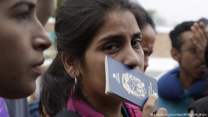 A Venezuelan woman holding up a passport in Peru