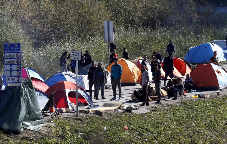 A group of migrants attempting to cross into Croatia hold banners as they gather near the Maljevac border crossing, Velika Kladusa, Bosnia and Herzegovina, on October 25, 2018 | Photo: EPA-EFE/FEHIM DEMIR