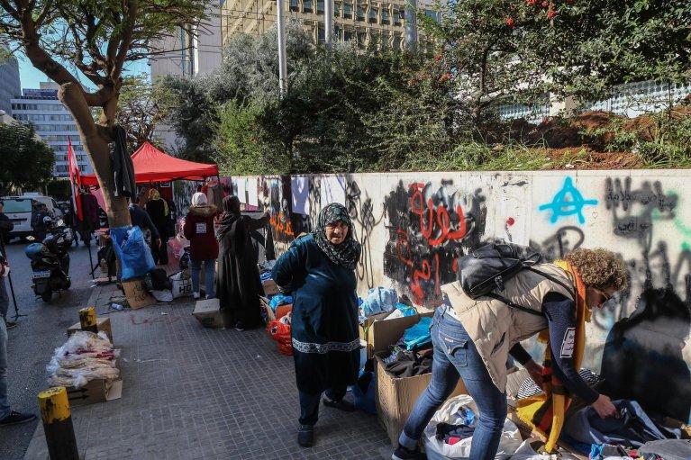 أشخاص يتفحصون الملابس والأحذية التي حصلوا عليها تبرعا من المواطنين، أمام البنك المركزي في شارع الحمراء ببيروت. المصدر: إي بي إيه/ نبيل منذر.