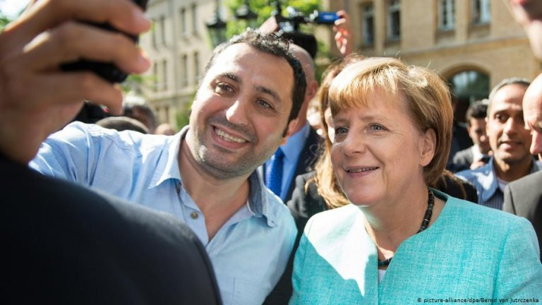 Refugee in Berlin taking selfie with Angela Merkel in 2015 | Photo: Picutre-alliance/dpa/B.Jutrczenka