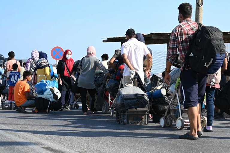 Asylum seekers waiting in a line with their belongings as refugees and migrants from the destroyed Moria camp wait to enter a new temporary camp near Kara Tepe on Lesbos island   Photo: EPA/VANGELIS PAPANTONIS