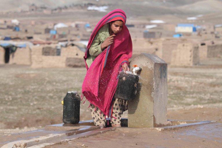 فتاة أفغانية نازحة تملأ صفيحة مياه