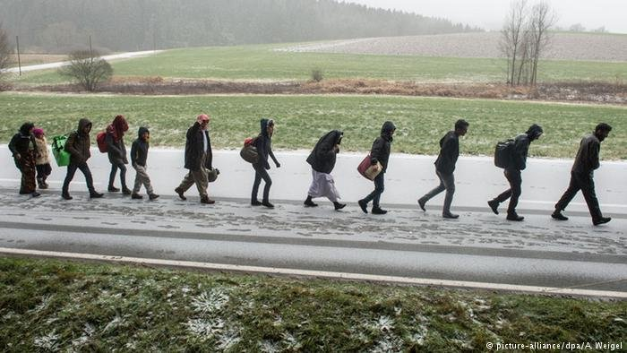 A line of people walking to Germany across the Austrian border