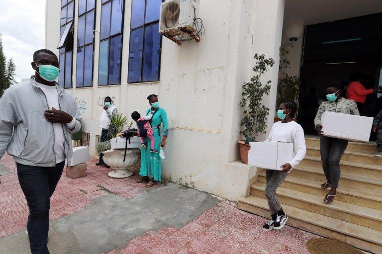 ANSA / مهاجرون أفارقة يحملون صناديق المساعدات التي تم توزيعها في مقر بلدية مدينة رواد في تونس. المصدر: إي بي إيه/ محمد مسارة.