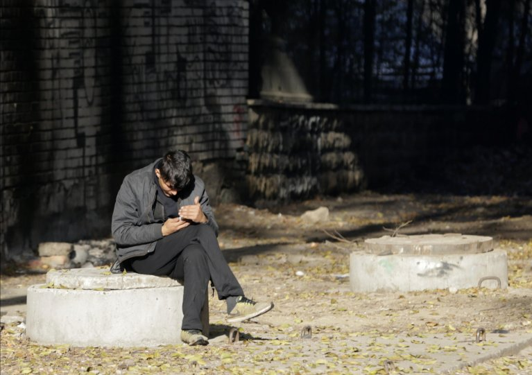 A migrant from Afghanistan looks at his phone in Belgrade, Serbia   Photo: EPA/ANDREJ CUKIC