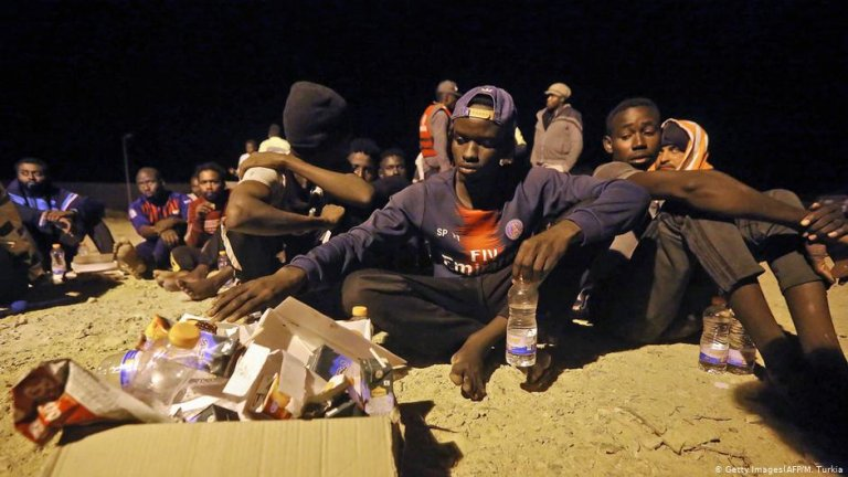 African migrants sit in the sand | Photo: Getty Images/AFP/M.Turkia
