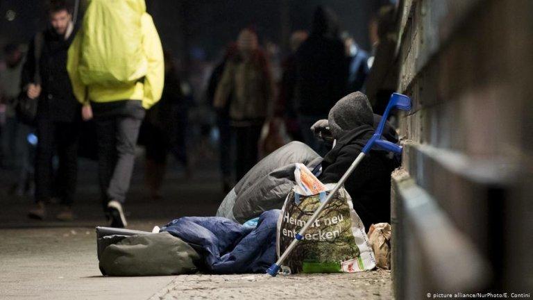 People walk past a homeless person in Frankfurter Allee in Berlin | Photo: Picture-alliance/nurPhoto/E.Contini