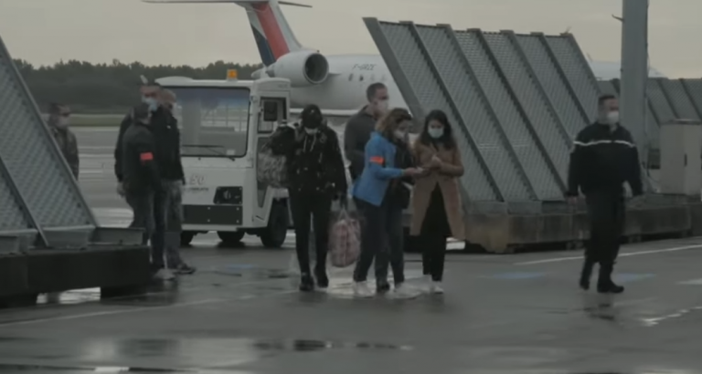 Ismail in the center, holding his bags is accompanied by more than 15 officials and police as he exits the flight from the UK to France | Source: Screenshot Channel 4 News