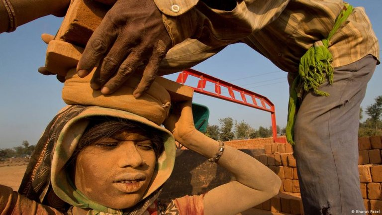 Woman carrying heavy load at construction site in India | Photo: Bharat Patel