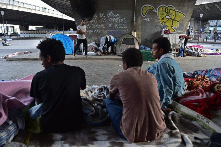 CHRISTOPHE ARCHAMBAULT / AFP  Des migrants installés à la porte de La Chapelle, à Paris en juin 2017.