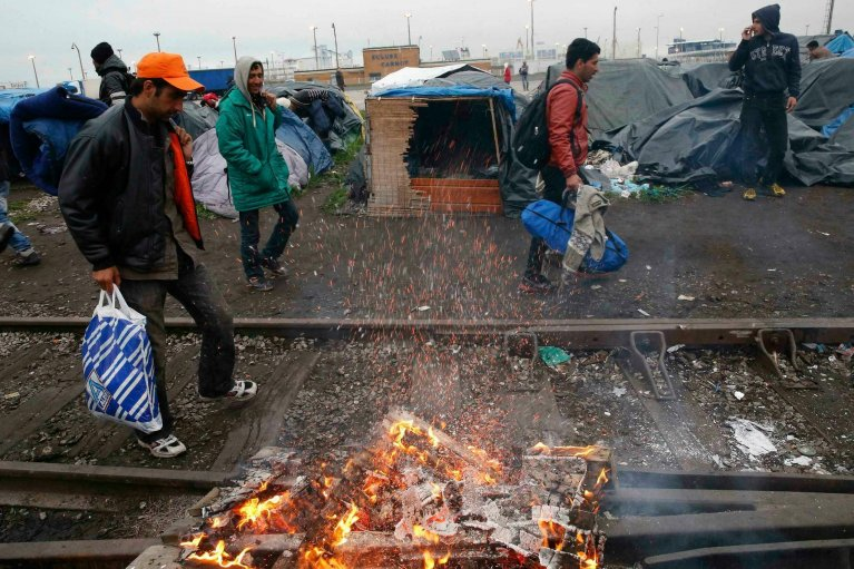 Migrants leave their camp in Calais where they have been staying for weeks in the hope of reaching England   Photo: Pascal Rossignol / Reuters