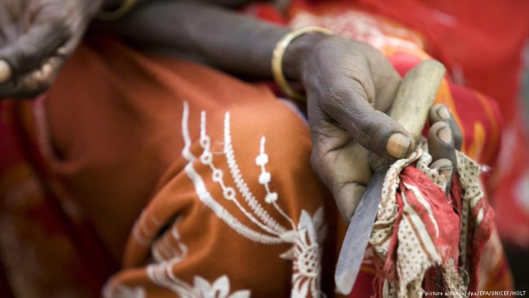 A former practitioner holds a tool she used to practise FGM