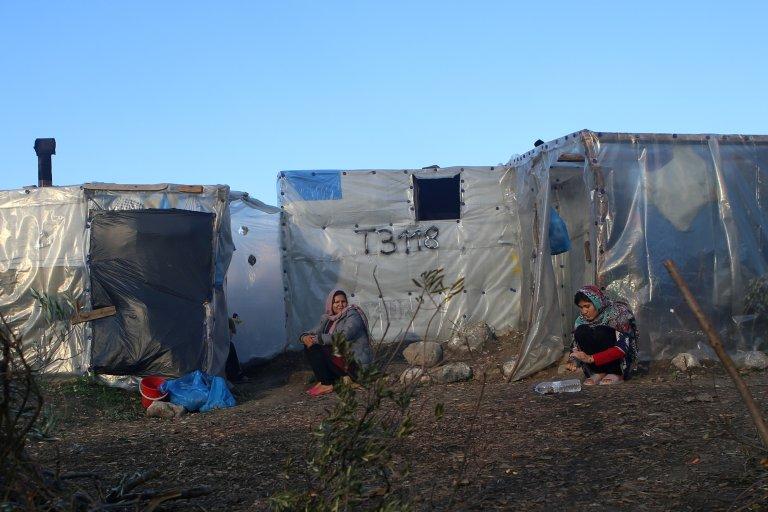 Des femmes sont assises à côté de tentes de fortune près du camp de Moria sur l'île de Lesbos en Grèce. Crédit : Reuters