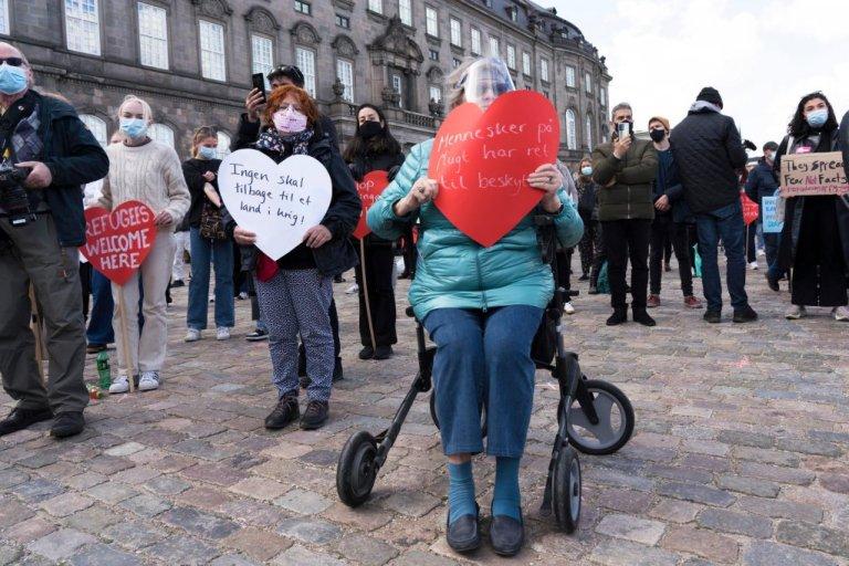 """""""للهاربين الحق في الحماية""""، هذا ما كتبته إحدى المشاركات في مظاهرة سابقة ضد تشديد سياسة الهجرة الدنماركية، وأوامر الترحيل. كوبنهاغن في 21 أبريل 2021. المصدر: AP"""