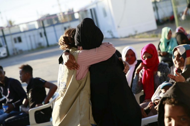A refugee hugs UNHCR staff as they meet at the Gathering and Departure Facility in Tripoli, Libya | Photo: UNHCR/Mohamed Alalem