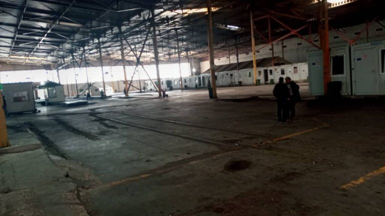 """The immense, hangar-like interior of Bosnia's Bira camp lined with containers that house migrants. 