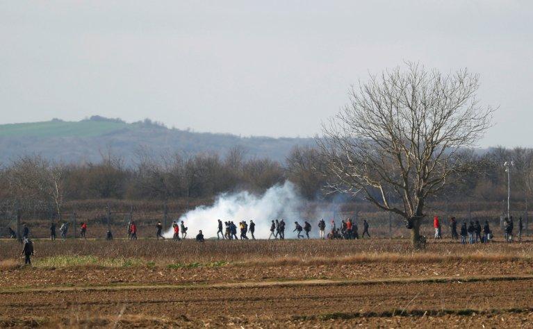 Des migrants marchent parmi les gaz lacrymogènes vers la frontière greco-turque, le 2 mars 2020. Crédit : Leonhard Foeger / Reuters