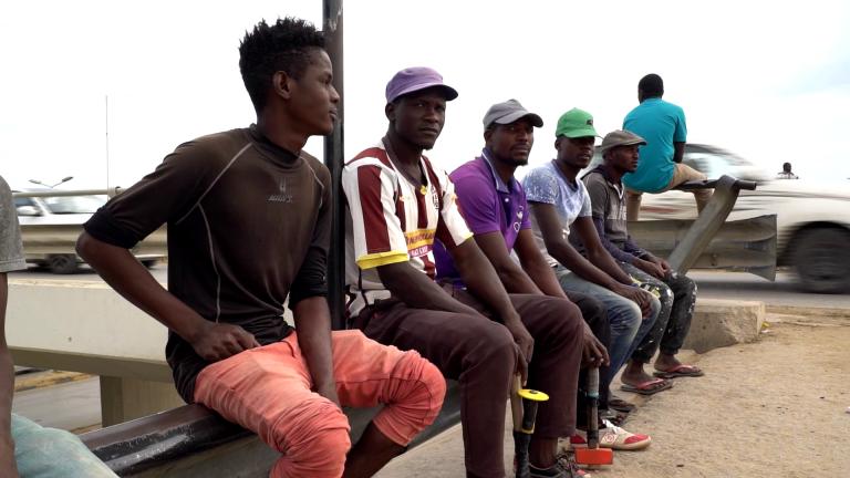 Des migrants africains attendent au bord d'une route près de Tripoli dans l'espoir de décrocher un petit job. Crédit : Julie Dungelhoeff / France 24