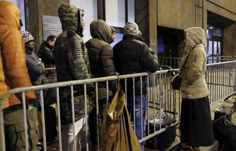 Migrants, some of them believed to be asylum seekers, queue in front of the Immigration Office in Brussels (Credit: ANSA/EPA)