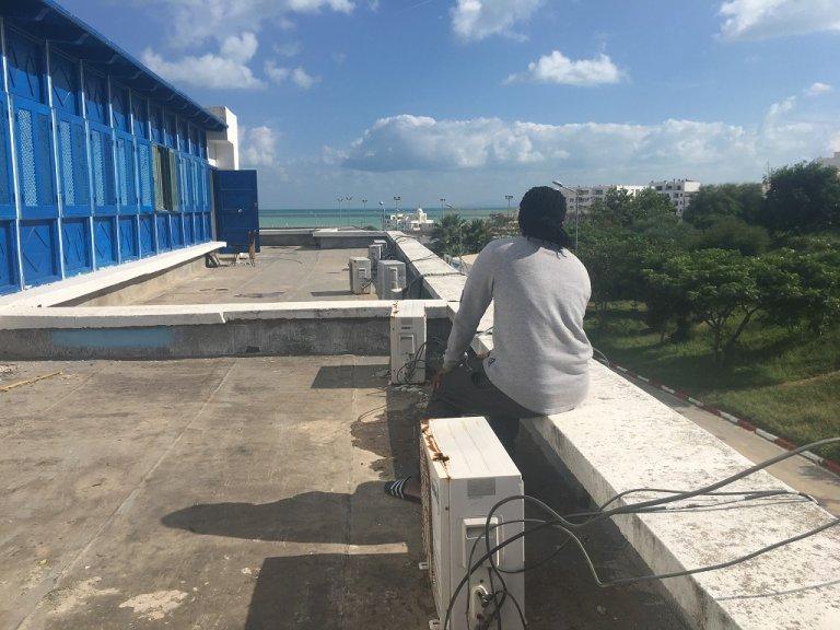 Ahmed sur le toit de l'immeuble où ce migrant ivoirien a été caillassé par des Tunisiens. Crédit ; InfoMigrants