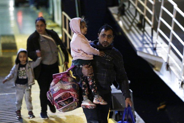 """ansa / لاجئون يحملون أطفالهم لدى وصولهم على متن سفينة """"بلو ستار 2"""" من جزيرة ساموس إلى ميناء بيرايوس بالقرب من أثينا. المصدر: إي بي إيه/ يانيس كوليسديس."""