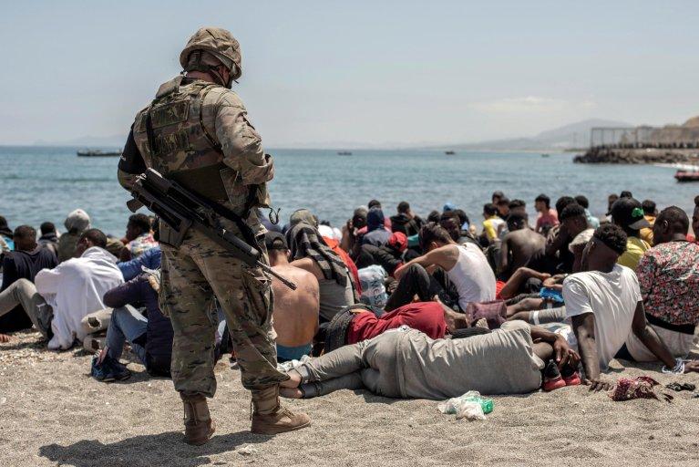 جندي إسباني ينظر لمهاجرين وصلوا سباحة عبر الحدود إلى مدينة سبتة. المصدر: إي بي إيه/ بريز لورنزو.