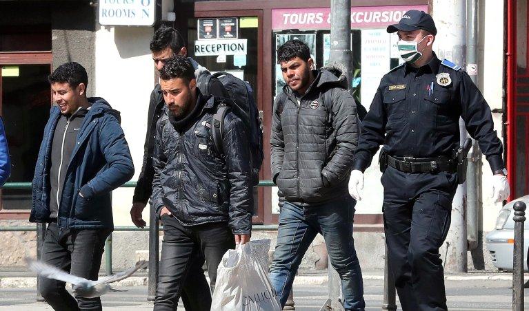 ANSA / ضباط من الشرطة البوسنية يصطحبون مهاجرين إلى أحد مراكز الاستضافة في العاصمة سراييفو. المصدر: إي بي إيه / فيهم دمير.