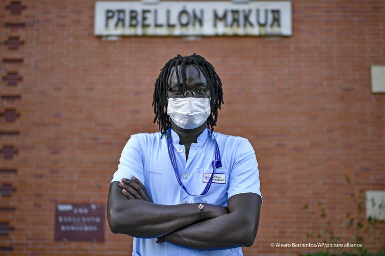 Mbaye Babacar Diouf poses for a photo wearing his nurse's uniform at Basurto hospital in Bilbao, northern Spain | Photo: Alvaro Barrientos / AP / picture-alliance