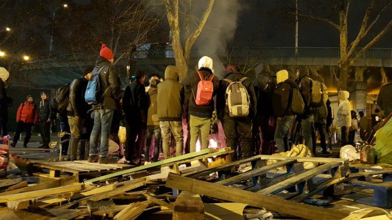 Des migrants attendent autour d'un feu d'être évacués du campement de la Chapelle, le 29 janvier 2019. Crédit : Anne-Diandra Louarn / InfoMigrants