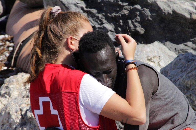 Luna Reyes, a Spanish Red Cross member, hugs a migrant who arrived swimming to cross the border of Tarajal in Ceuta | Photo: EPA/REDUAN
