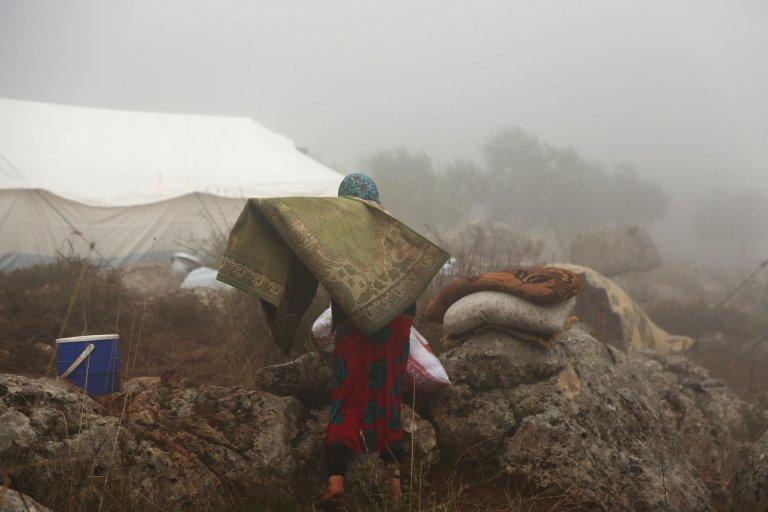 نازحة سورية تحمل سجادة لوضعها داخل خيمة، بعد فرارها من العنف في بلدة معرة النعمان قرب الحدود مع تركيا. المصدر: إي بي إيه/ يحيى نعمة.