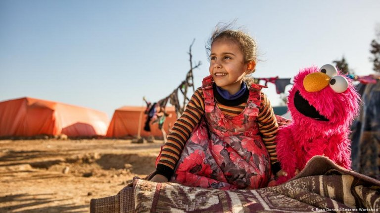 A girl and Elmo at a refugee camp | Photo: Ryan Donnell/Sesame Workshop