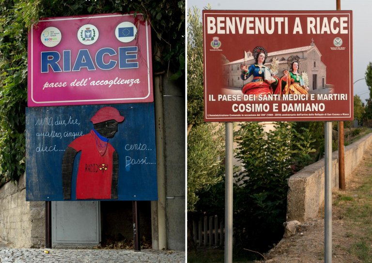 On the left, the old sign at Riace's entrance and, on the right, the one that replaced it, dedicated to the Saints Cosmas and Damian | Photo: ANSA