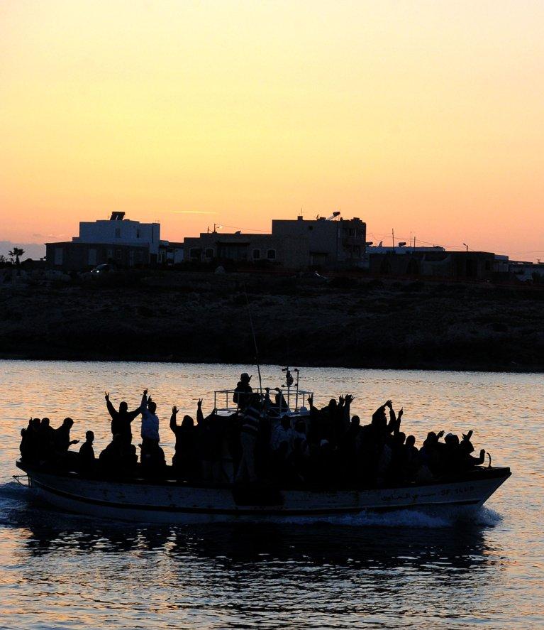 قارب يقل مهاجرين تونسيين يدخل إلى ميناء لامبيدوزا. أنسا/ أرشيف