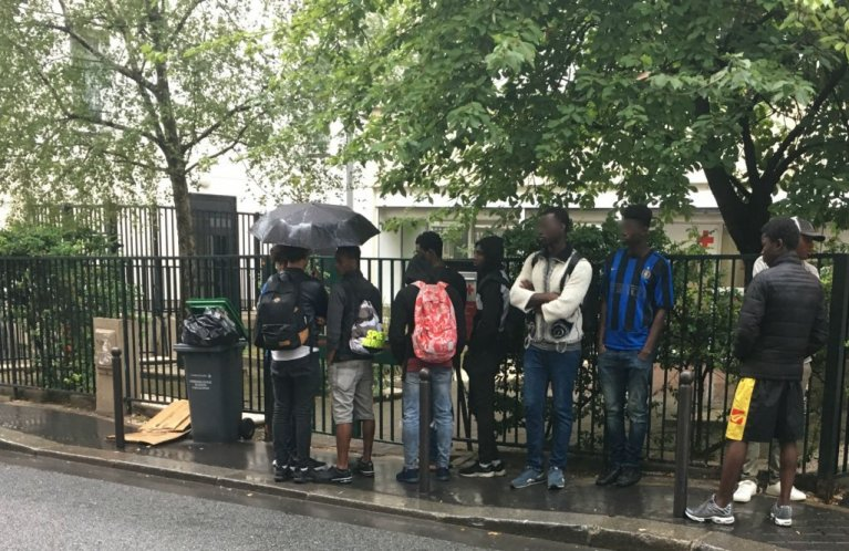 Youths line up outside the offices of Demie, an evaluation unit run by the Red Cross that is responsible for officially recognising unaccompanied minors in Paris. (Photo credit: InfoMigrants)
