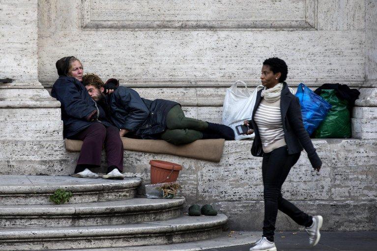 """ANSA / مشردون يجلسون أمام مدخل كنيسة """"سانت أندريا ديلا فالي"""" في روما. المصدر: أنسا/ ماسيمو بيركوزى."""