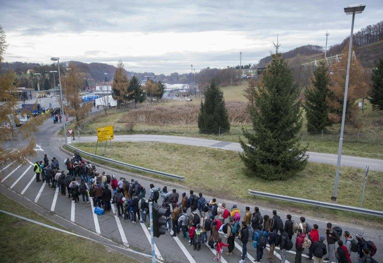 Migrants wait in line at the Slovenian-Austrian border in Spielfeld, Austria   Photo: EPA/ERWIN SCHERIAU