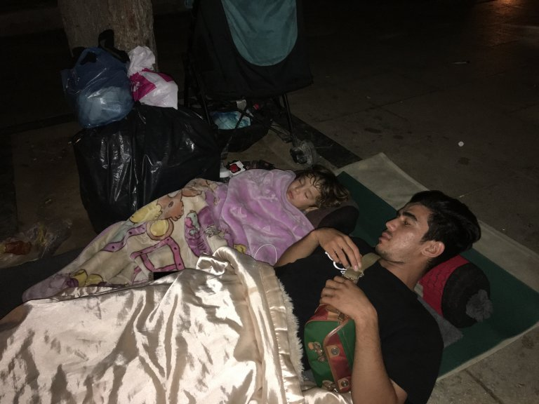 A young Afghan man and his son sleep on the ground in Victoria Square, Athens | Photo: Marion MacGregor/InfoMigrants