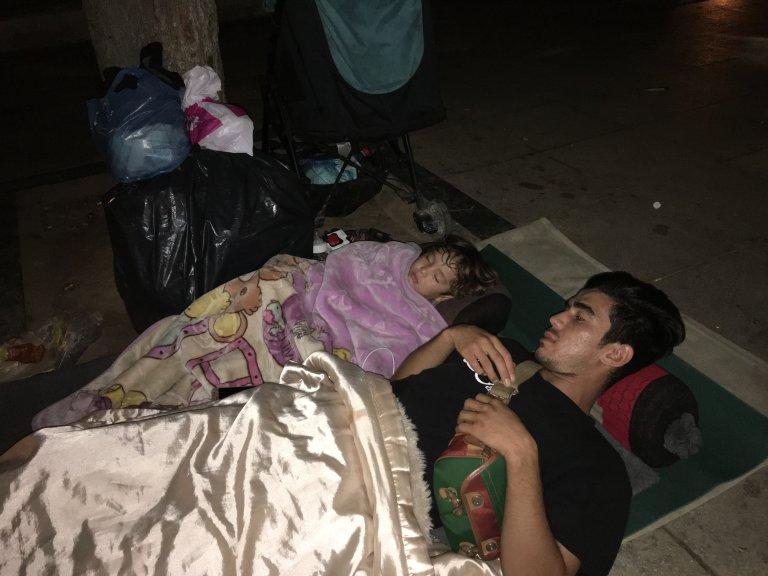 اتن، پارک ویکتوریا، یک مهاجر جوان از افغانستان و پسرش بر روی زمین به خواب رفته اند./عکس: ماریون مک گریگور/اینفومایگرانتس