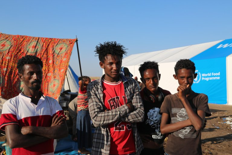 A handout photo made available by the UN World Food Programme (WFP) shows Ethiopian refugees who fled the conflict in Ethiopia's Tigray region posing for a photograph in Hamdayet Reception Center, in the border town of Hamdayet, Sudan, 17 November 2020 | Photo: EPA/LENI KINZLI