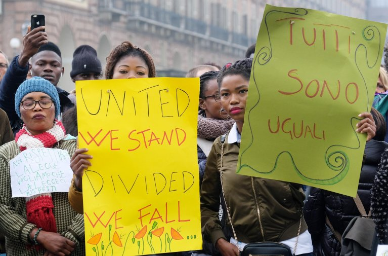 "A migrant demonstration in Piazza Castello in Turin. Sign in Italian says ""We are all equal"". Credit: ANSA/ALESSANDRO DI MARCO"