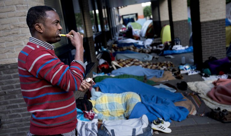 An asylum seeker from Somalia in front of the Dutch Immigration and Naturalization Service in Hertogenbosch, Netherlands   Credit: ARCHIVE/EPA/JERRY LAMPEN