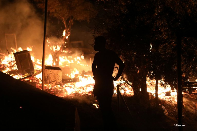 Refugees and migrants stand next to flames as a fire burns at the Moria camp on the island of Lesbos, Greece, September 9, 2020 | Photo: REUTERS/Elias Marcou