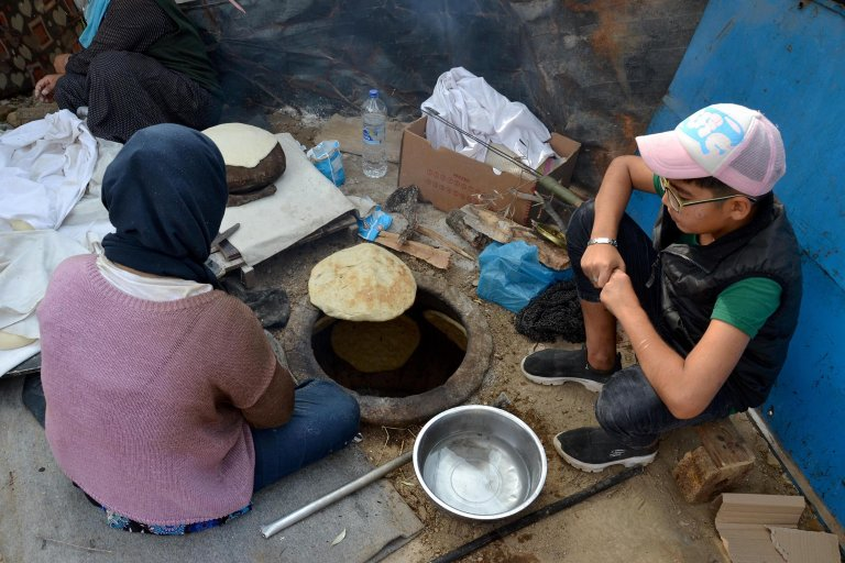 Migrants bake 'naan' bread, an Indian traditional flat bread in an underground oven they made themselves near the Moria refugee camp, Lesvos island, Greece | Photo: EPA/STRATIS BALASKAS
