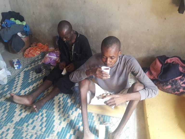 Two migrants are given food and water by the organisation Al-Salam in Bani Walid, where our Observer was enslaved and tortured.