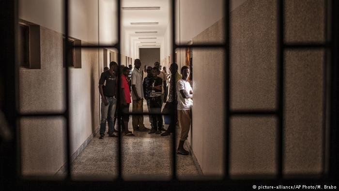 Migrants stand at a hall in a detention center, near Misrata, Libya