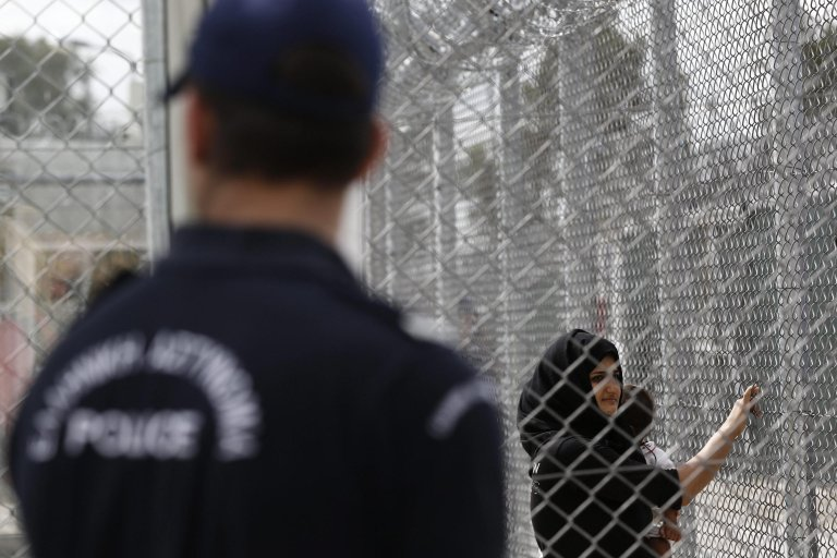 An Iraqi woman stands behind a fence as a police officer stands guard at Amygdaleza pre-departure center for refugees and migrants who are asking to return in their countries, in Athens, Greece. Credit: EPA/YIANNIS KOLESIDIS