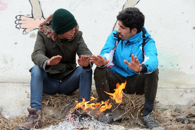 """ansa / مهاجران أشعلا النار في العراء في محاولة للحصول على الدفء أثناء إقامتهما في مخزن مهجور في منطقة أداشيفاتش في صربيا بالقرب من الحدود مع كرواتيا / المصدر: """"إي بي إيه""""/ كوتسا سوليمانوفيتش."""