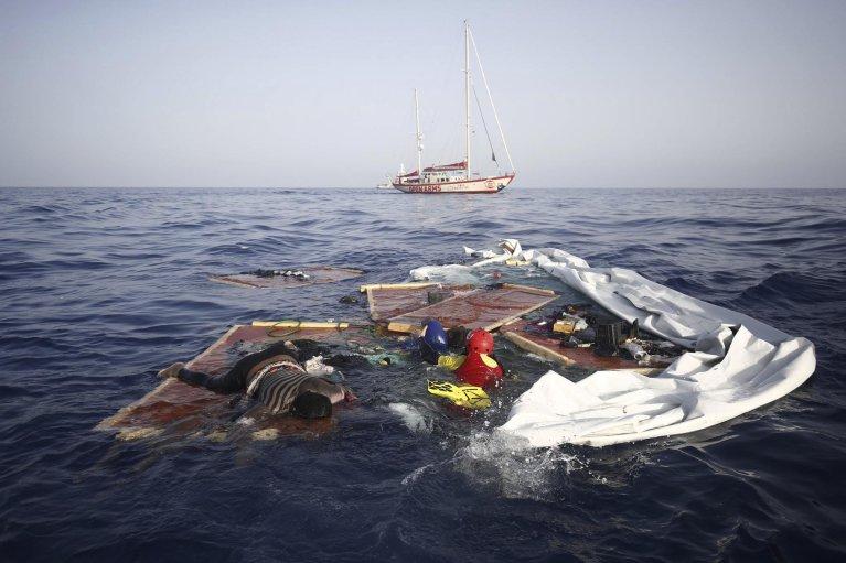 """ansa / عمال إنقاذ من منظمة """"بروأكتيفا أوبن آرمز"""" الإسبانية غير الحكومية ينتشلون جثتي مراهق وطفل من بين حطام أحد قوارب المهاجرين. المصدر: بروأكتيفا أوبن آرمز"""